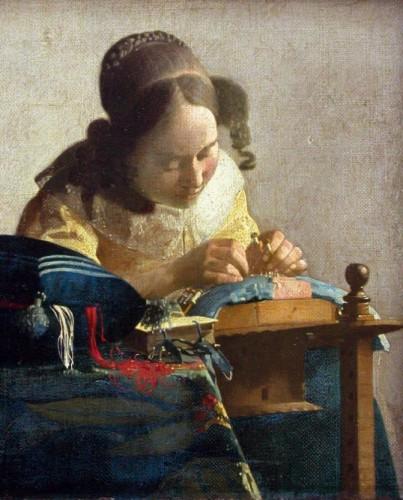 Une femme se penche sur son ouvrage tenant fermement ses fuseaux et ses épingles.
